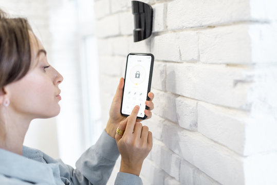 Woman controlling alarm system with smart phone and special mobile application wireless, standing near the motion sensor indoors