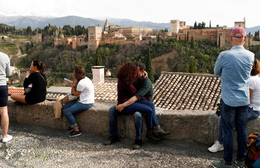 A couple kiss at San Nicolas viewpoint in front of La Alhambra which is closed to visitors due to the coronavirus outbreak, in Granada
