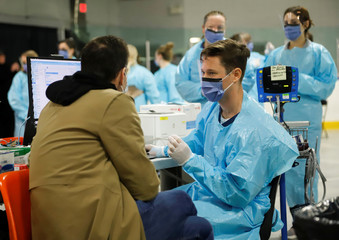 Medical staff assess someone portraying the role of a patient as they prepare to receive people for coronavirus screening at a temporary assessment center at the Brewer hockey arena in Ottawa