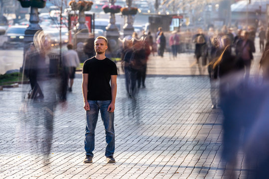 The man stands on the crowded street