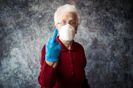 Old grandmother protect herself from coronavirus infection with medical gloves and respirator mask