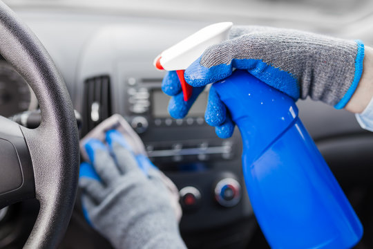 Close up of man hands using microfiber cloth and spray bottle while cleaning car interior.