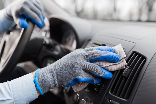 Close up of worker hand cleaning car dashboard.