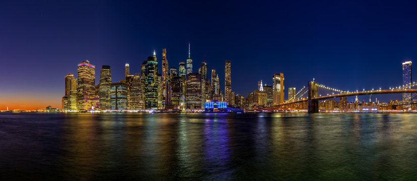 Panoramic image of lower Manhattan and the Brooklyn Bridge at night with the Hudson river reflecting the lights.