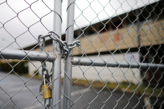 A lock and chain closes the fence around a former motel that was bought by King County as a coronavirus quarantine facility in Kent