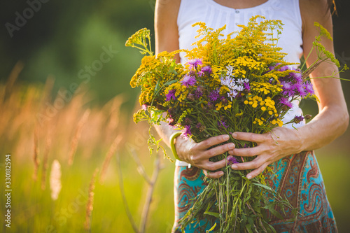 Beautiful bouquet of bright colorful wildflowers in the hands of a young girl walking in the field in the evening. Toning