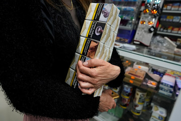 A woman holds a pack of cigarettes in a tobacco shop at the Vallecas neighborhood, in Madrid