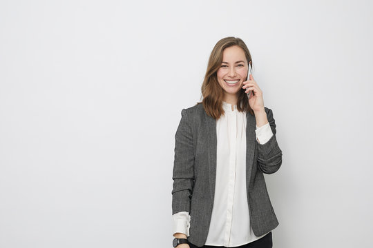 Happy beautiful Businesswoman is talking on the phone on a white background