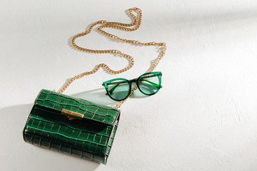 Wall Mural - Fashion green handbag with sunglasses on white background. Flat lay, top view. Summer fashion concept