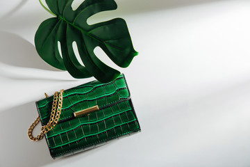 Wall Mural - Fashion green handbag with tropical leaf. on white background. Flat lay, top view. Summer fashion concept
