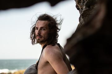 Männliches Model mit langen Haaren am Meer vor Felsen 1; Südafrika