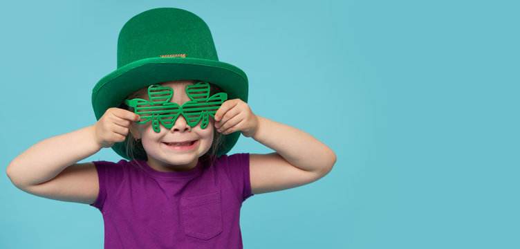Funny little child girl in green Patricks hat with clover glasses on color background. St. Patricks Day celebration. Advertising space