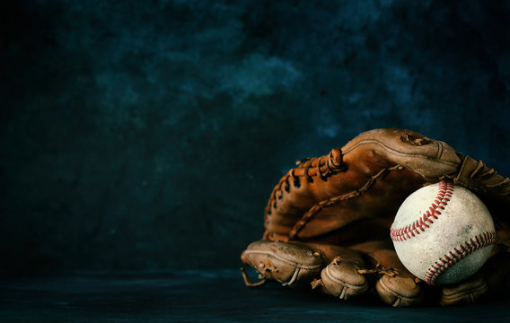 Baseball glove with ball close up in studio with dark texture backdrop, copy space for sport graphic concept.