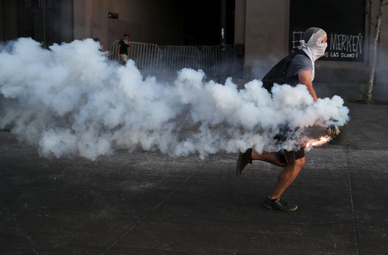 A demonstrator runs before launching a molotov cocktail during a protest against Chile's government in Santiago