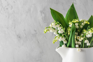 Foto op Canvas Lelietje van dalen bouquet of spring lily of the valley flowers in vase on concrete background with copy space