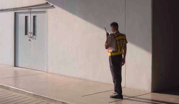 Asian security guard in safety vest walking on sidewalk and using walkie talkie or portable radio transmitter with sunlight and shadow on surface of staff room door in grey cement wall background