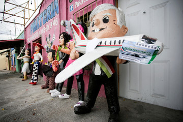 A pinata of Mexico's President Andres Manuel Lopez Obrador holding a scale model of the presidential plane and mock lottery tickets for its raffle, is pictured outside the workshop of artisan Dalton Ramirez in Reynosa