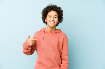 African american little boy isolated person pointing by hand to a shirt copy space, proud and confident