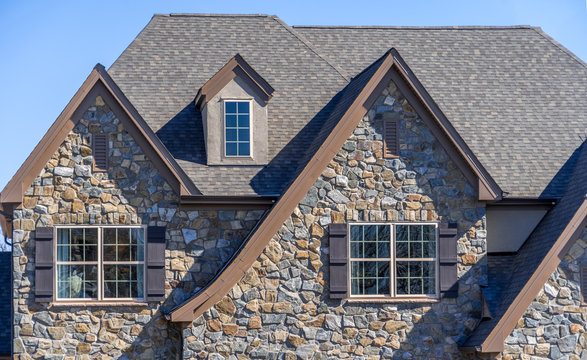 Double gable with dark stone veneer siding,  with triangle shape peaks, on a pitched roof attic at an American single family home neighborhood USA, double sash windows w/ matching dark shutters