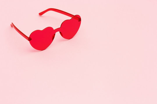 Minimal style fashion photography with heart shaped red glasses on pink paper background. Pink modern sunglasses.  Trendly summer concept. Copy space.