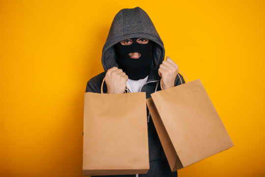 Thief with paper bags. The guy in the balaclava steals purchases from the store. Masked man on yellow background