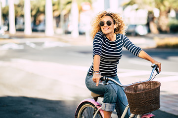 Beautiful and cheerful adult young woman enjoy bike ride in sunny urban outdoor leisure activity in the city - happy people portrait - trendy female outside having fun Fototapete