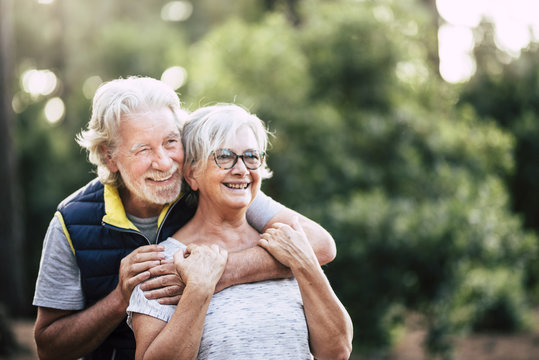 Old mature retired senior people smile and enjoy the love couple during outdoor leisure activity together - green forest and wood in background for environment concept