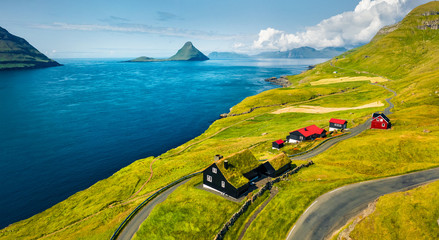 Deurstickers Noord Europa View from flying drone. Sunny summer view of Velbastadur village with typical turf-top houses. Attractive morning scene of Streymoy island, Faroe, Denmark, Europe.