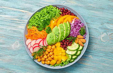 Buddha bowl salad with avocado, tomato, lettuce, cucumber, red cabbage, chickpeas, pomegranate. Vegan and balanced food concept. Fresh rainbow mix green salad on blue wood