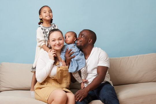 Portrait of happy multiethnic family sitting on couch at home and looking at camera. Black father, white mother and two daughters. Eldest leaning on mother from behind. Youngest is in father's arms.