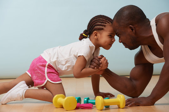 Handsome black young father is arm wrestling with his cute little daughter on the floor at home. They looking at each other angrily, trying to show their resolve. Grimacing at each other.