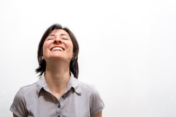 Portrait of a young happy brunette woman standing on a white wall, smiling with closed eyes in a peaceful manner. Positive human emotions.