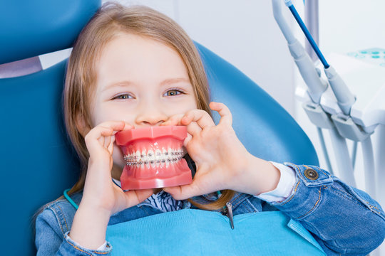 Little cute girl is sitting in dental blue chair in clinic, office. Funny kid patient is holding jaw layout in front of mouth like her smile. Visiting doctor dentist orthodontist with children.