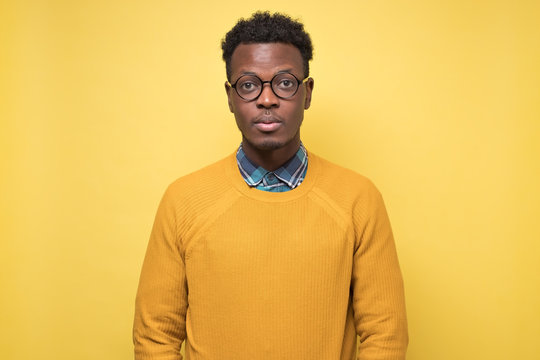 Young african american man in yellow sweater looking serious at camera. Studio shot