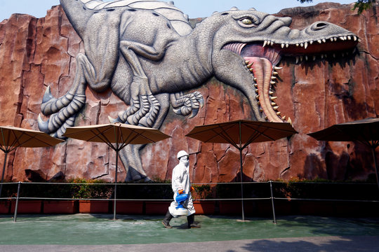 A worker wearing protective suit passing by near a wall where is depicted a dinosaur at Dufan, in Jakarta, Indonesia