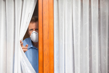 Mature man put under quarantine at home or at a hospital because of an infection or coronavirus looking sorrowful out of  a window