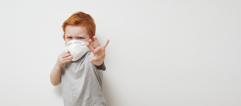 Redhead boy is saying stop and holding his hands up infront of him to Stop Corona virus Covid-19 / 2019nCov while wearing a protecting mask.