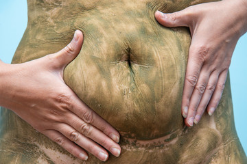 Cellulite Removal Treatment. Skin care and treatment. Close up portrait young relaxed woman having anticellulite sea weed mud procedure of body.