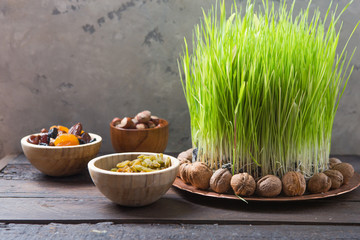 Happy Nowruz holiday background. Celebrating  various dried fruits, nuts, seeds, light background with green grass wheat, copy space top view