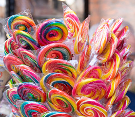 Colorful bright assorted candy canes and rainbow colored spiral lollipops with scattered marmalade, jellybeans and different colored round candy.