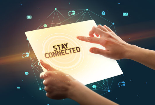 Holding futuristic tablet with STAY CONNECTED inscription, social media concept