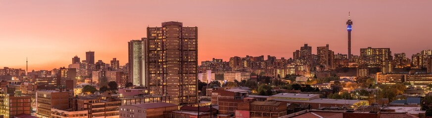 Wall Murals Salmon A beautiful and dramatic panoramic photograph of the Johannesburg city skyline, taken on a golden evening after sunset.