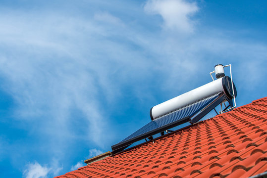 Solar water heater boiler on rooftop, beautiful washed white clouds on blue sky.