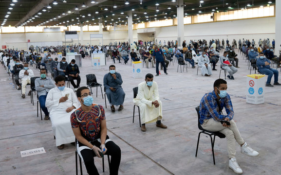 Expatriates wait for mandatory coronavirus testing in a makeshift testing centre in Mishref