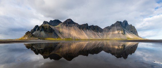 Foto op Canvas Blauwe hemel Beautiful shot of a mountain reflected on the water in Stokksnes, Iceland