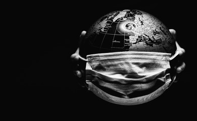 Hands of little child holding globe sphere, planet map covered with medical protective mask isolated on black background. Concept of COVID-19 pandemic infection. Black and white image