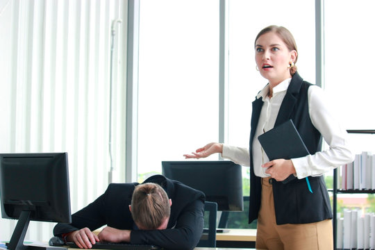 Staff officer taking a nap on the office desk, employee sleeping at the workplace. Angry confused boss caught tired lazy employee sleeping at office