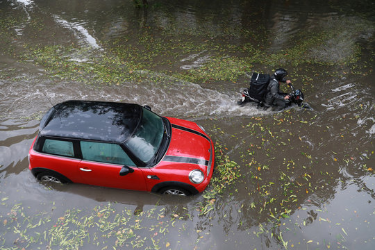 A man rides a bike past a car stuck in flooded water after heavy rains and hailstorm in New Delhi