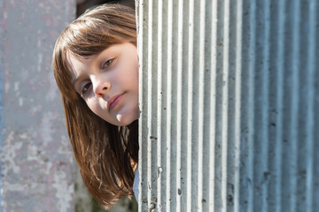 Young girl looks out from behind the wall
