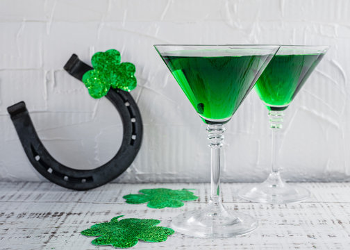 St. Patrick's Day concept. Green drink, green cocktail in a glass, horseshoe and clover leaf